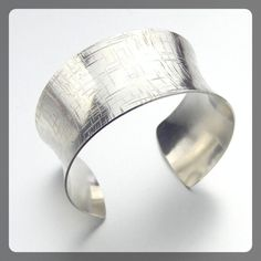 Add glam to any outfit wit this Sterling Silver Anticlastic Cuff Bracelet featuring a deep pattern reminiscent of a criss cross textured pattern on the outside, complemented by a highly polished finis
