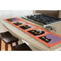 """Scaredy Cat Table Runner Kit- This quick kit allows you to choose to make a quilt, table runner, or a pillow or two with a black cat peeking at you! Use your favorite applique technique along with Deena Rutter's pattern and fabrics for the top and binding to make the 57"""" x 13"""" table runner shown. Best of all, it's so easy it can be finished in on weekend!"""