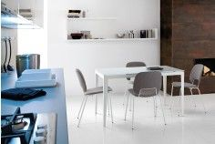 Designed for compact spaces, this table has a simple linear design. With extending functionality, the white lacquered steel frame placed combined with the white tempered glass top presents a clean and contemporary profile. The Traffic Chair features a simple and popular design with an unusual twist and shape for the chair back. Chair has white lacquered frame and taupe upholstery.