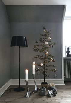 Minimalistic Christmas tree with ornaments in muted colors with silver and white as a recurring element.