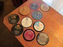 Drink coasters I cut the center label section from vinyl record albums, waterproofed them and made a woodholder.