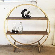 Two wooden shelves span a frame of gold-toned hoops