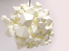 """NaCl Light Shade by James Patmore  """"'NaCl' is an organic cluster of geometric shapes. Based upon the sporadic formation of salt crystals the light-surround mimics their growth whilst keeping a sensitivity to the light, using paper to manipulate the light source enabling the opportunity to explore the ranging tonal qualities. Like its inspiration the piece has the possibility to grow into a dramatic installation piece."""""""