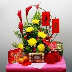 Chinese new year arrangement of gold chrysanthemums and red tropical ginger (Alpinia)