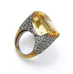 A YELLOW SAPPHIRE, DIAMOND, PLATINIUM AND GOLD RING, BY CARTIER     CARTIER   Bague en or jaune et platine, ornée en serti transversal d'un saphir jaune rectangulaire taillé en coussin, l'épaulement entièrement serti de diamants taillés en brillant et de deux diamants taillés en baguette. Le tour de doigt fileté. Signée Cartier, numéro illisible. Exécutée vers 1980.   Poids de la pierre : env. 28 cts   Tour de doigt : 49,5 - Poids brut : 18,5 g   Provenant de l'écrin de Mme Josette Dey.