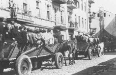 Jews, mostly children, proceed on horse-drawn wagons to assembly points for deportation. They are guarded by the Jewish police. Lodz ghetto,...