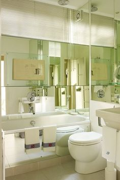 Discover small bathroom design ideas on HOUSE - design, food and travel by House & Garden. A backdrop of mirror-glass panelling cheats this bathroom's compact proportions.