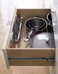 If you are looking for a space-saving kitchen hack that is not only efficient, but also attractive, look no further. Use a simple tension rod inside a kitchen drawer to keep lids neat and tidy. Click the pin for more organization tips that look as good as they work. #organizingtips #organization #organizing #organizationtips #organizingtips #declutter #decluttering #homestorage #homeorganization