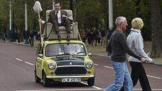 Komiker Rowan Atkinson sitzt in einem Sessel auf einem Mini
