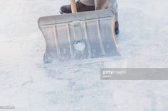 Stock Photo : Close-up of a man shoveling snow with a snow shovel standing on ice. Winter.