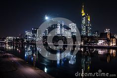 A long exposure shot of the business district in Frankfurt over the Main river. The tall buildings of `Mainhattan` are reflecting in the frozen January waters.