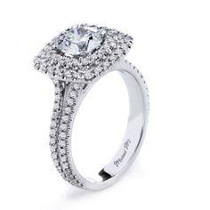 Dual strands of unique U-set pave diamonds support a double pave cushion-cut halo for a bold modern design.