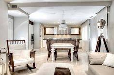 Un salon de détente dans la même pièce que la cuisine à l'ameublement chic en beige claire et blanc