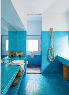 Une salle de bain bleue recouverte de mosaïques