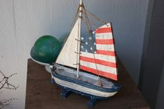 Here is a very charming Americana style sail boat with wooden sails, blue, red and white coastal color. Each piece has been hand carved and hand painted with great attention to details.  Specifications:  - Size:16 INCHES (40cm)  - Type: wood  - Color: white, red and blue    Perfect art piece for your cottage or beach house. Great Americana decor!