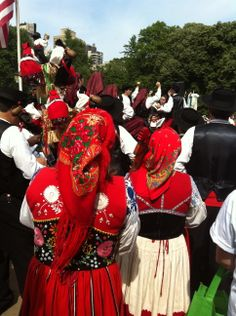 Portuguese folk dancers in the Lavradeira (left), Domingar (right), and Mordoma costumes (back) from the group Danca Na Eira