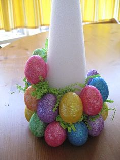 Easter egg tree.   Put a dab of glue on egg then hold it in place for a few seconds.  Start at the bottom and work your way up.  Although this pic shows grass being put on along the way, wait till the end to fill the holes with grass.  It's much easier.  Use a pencil to push the grass into the gaps well.  Make sure you let the glue dry well before filling the gaps.