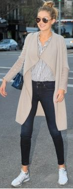 Gigi Hadid wearing skinny jeans, a stripe blouse, and waterfall sweater