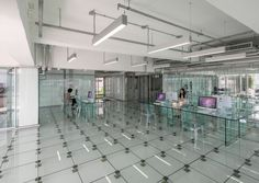 A view inside the building shows chairs and desks made of glass