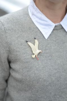 ash grey sweater, pale blue collar and whimsical pin.