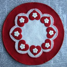This candle mat is made out of wool felt and measures about 10 inches across. It is made with a pretty red and creamy white colored felt. I
