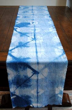 "Hand-dyed linen blend table runner with organic indigo in an itajime  shibori pattern. Finished fringe edges.   I use an organic indigo fructose vat that is completely chemical free.  17"" x 94"". Linen and bamboo blend.   I recommend hand washing in cool water to preserve color inten"