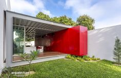 The red feature wall on this home makes it super cool. Fachada principal by Grupo Arquidecture