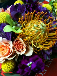 Up close & personal with some Pincushion Protea, purple Alstromeria & Stock, yellow Billy Balls, & coral Spray Roses in a playful wedding bouquet. www.fioreofpensacola.com