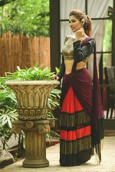 A red and black colour blocked georgette pre stitched sari with purple pallu and metallic chain fringe. It comes along with laser cut leather blouse and herringbone fabric back. #WedMeAlready #WedMeDesigner #WedmeOffTheRamp #WedMeCallToBuy #myotr #OffTheRamp For more details and designs please visit offtheramp.com or call 8447158533.
