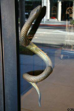 Bronze snake door handle slithers through glass door on Rodeo Drive store. Beverly Hills, CA.