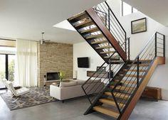 escalier tournant en métal noir et bois massif, carrelage sol gris taupe et canapé droit