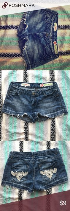 """Size 9 Hot Kiss denim shorts. These shorts feature a """"worn"""" look with a light washout on the thighs and feathered tears on the end but are dolled up with a bit of lacework on the back pockets. They are a size 9 by Cicis but I wear a size 5 and they still fit great! Hot Kiss Shorts Jean Shorts"""
