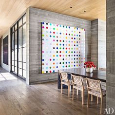 A Damien Hirst painting presides over the dining room, where Alvar Aalto chairs by Artek surround a bespoke table; the large canvas in the hallway is by Sterling Ruby.