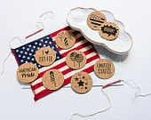 """Americana - Adorable, patriotic July 4th, flat circle cork stickers with adhesive backing and black ink for cards, pocket pages, scrapbook pages, envelopes, and so much more! Great for any arts and crafts project. Each package contains 9 stickers. 3 Word Art - """"United States"""", """"American Pride"""" and """"I """"heart"""" July 4th"""" 6 Designs - 2 Firecrackers, American heart, boom, balloons, and stars. Available on Etsy"""