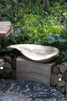 Curved organically shaped wooden seat w/ mosaic pebble floor  --  could be a cement water fountain feature