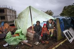 Credit: Mugur Varzariu/AFP A Roma family of Turkish origin sit under an improvised shelter to protect themselves from heavy rain in Eforie Sud, Romania. Authorities evicted around 100 Roma from a town near the Black Sea coast without providing them with alternative housing