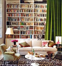 """#Living Room #Library Hide floor to ceiling #books and cabinets behind a tall green velvet drape.  I like the painters ladder.  This is a great way to hide """"stuff"""" while keeping it classy."""