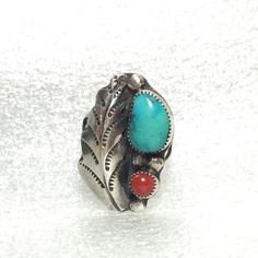 """Vintage Native American Turquoise Coral .925 Ring This beautiful sterling silver ring features a 1 ¼"""" long left-side feather softly encompassing a large turquoise cabochon to its top right with a small round coral cabochon underneath and nestled by three sterling dollops. This ring truly depicted 1970s Native American artistry. Size 7, 5.62 grams. Jewelry Rings"""