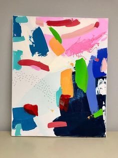 Smashing is an original, abstract painting on stretched canvas, measuring 16 x 20 inches. It is done in acrylic paint, with graphite line work. Smashing has lots of negative space with areas of blue and pink (and pops of addtional color). It is signed, dated, and titled on the back, so it
