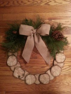 Wreath made from slices of log. Drill a small hole in one log slice in order to attach some twine for hanging, (this piece will be at the top of your wreath). To create a perfect circle, arrange the logs around the outside of a pot leaving space between each piece. Layer the next row on top, centering between the logs below. Secure the pieces together using hot glue. Lastly, embellish with artificial greenery and a bow.