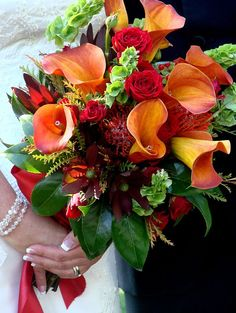 Orange calla lily wedding bouquet - This photo is from my daughter's wedding.  The red roses and orange calla lilies were stunning...the flowers even had crystals inside them.