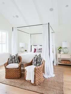 Chi cottage bedroom features a vaulted ceiling with white wood beams over an iron canopy bed fitted with a tan headboard accented with white sheers flanked by light wood farmhouse nightstands topped with recycled glass lamps alongside a pair of seagrass chairs accented with black and white pillows placed at the foot of the bed atop a jute rug.