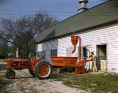 Farmer standing at an open barn door pouring corn into a belt-driven McCormick hammer mill powered by a Farmall C tractor. Antique Tractors, Vintage Tractors, Vintage Farm, Vintage Signs, Farmall Tractors, Old Tractors, John Deere Tractors, International Tractors, International Harvester