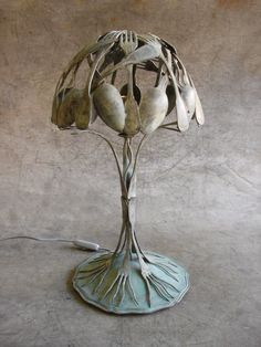 This sculpture serves both a functional and artistic purpose. It is a lamp, but it is also an art piece. The 'shade' of the lamp appears to be made up of several sculpted silverware items, and the resulting design is extremely interesting and eye-catching. It's intriguing because the artist sculpted spoons and forks, and the lamp itself rather than using real, ready-made materials.