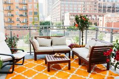 wow i need to live in the city now.  i love this bright punch of orange in the rug. balance out a loud rug with subdued furniture.  don't be afraid to go bold outside!