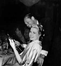 The actress Grace Kelly smiles happily at the camera during the celebrating party held just after the 27th Academy Awards in Romanoffs Restaurant, holding the Oscar in her hands; William Holden, who co-starred with Grace in the movie The Country Girl she were awarded for, as best actress, stands with her, gazing at the prize. USA, March 1955.