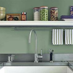 towel rod under the open shelf above the sink..