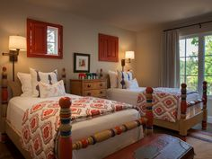 The children's bedroom in the guest house is kitted out with custom-made wooden beds and windows with red shutters. Textiles by John Robshaw, as well as linens designed by Violante