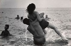 Garry Winogrand's 1952 photo of a young man hosting a woman into the surf at Coney Island