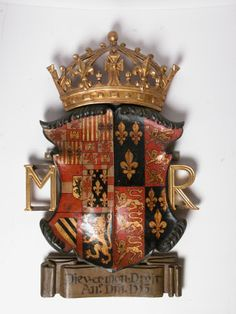 Carved heraldic shield painted black, gold and red summounted by a gold painted carved crown. Carved gold painted initials 'M R' on either side of shield. Badge of Mary Tudor, black painted inscription on brown painted banner below shield reads 'Dieu et mon Droit ANo DM 1553'. 'Philip of Spain and Mary Tudor. 1554 - Mary Tudor married Philip of Spain and Snowshill Manor was alienated to Francis Bulstrode and his wife Ann' (M. Jessup). Brown Paint, Gold Paint, Painted Initials, Mary Tudor, Tudor History, Black History Facts, Coat Of Arms, Image Collection, Badge